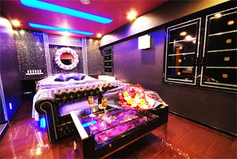 Inside a Japanese Love Hote - bright neon lights, wine, flowers, and a big bed