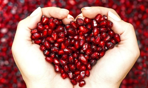 Hands holding pomegranate seeds to form a heart shape