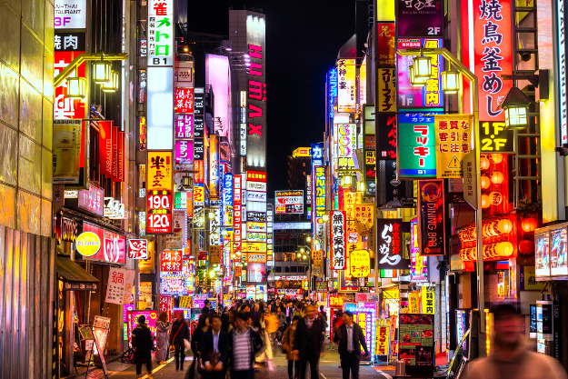 Downtown Tokyo street at night with bright neon signs