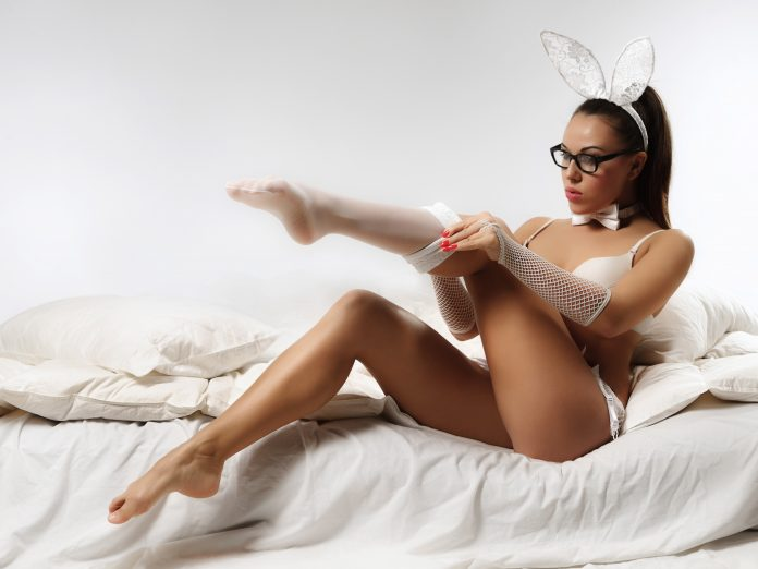Sexy woman in lace bunny ears putting on white stockings