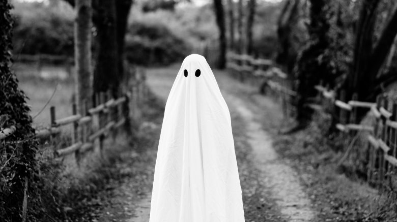 Person dressed as bedsheet ghost outside